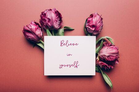 相信自己的句子在卡片上用美丽的一束牡丹风格的郁金香在粉尘的背景上,春假概念,复制空间