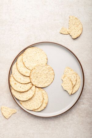 Healthy Snack from Free From Gluten and Free from Milk Crackers on Light Background. Tapioca, maize and soya crackers with sea salt and cracked black pepper