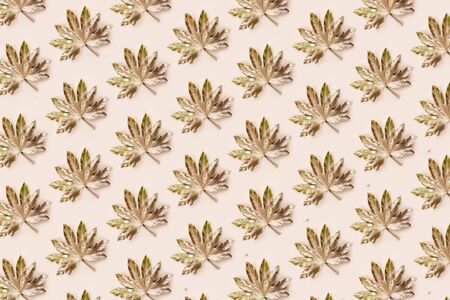 Beautiful Leaf Pattern. Leaves are painted in golden and copper metallic paint on pink background. Autumn minimalism. Isometric flat lay.