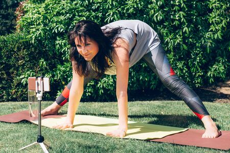 Happy woman is doing online yoga with smartphone on tripod during self isolation at her garden, no equipment workout, meditation tips for beginners, stay home and stay healthy concept