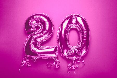 Silver Number Balloon 20 on pink background. Holiday Party Decoration or postcard concept with top view on blue background