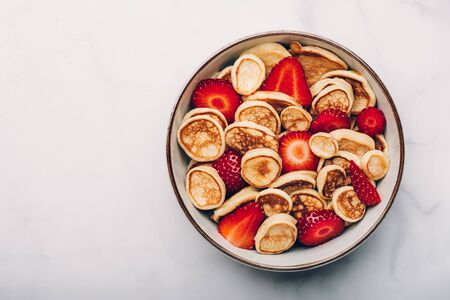 Trendy home breakfast with tiny cereal pancakes with piece of butter and fresh strawberries in the bowl. View from above.