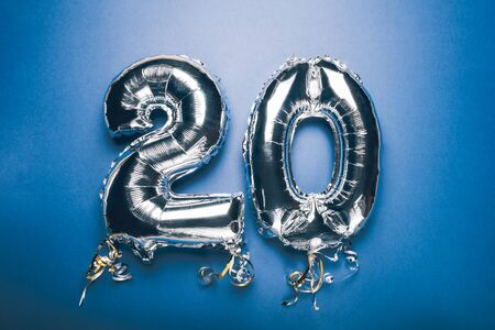Silver Number Balloon 20 on blue background. Holiday Party Decoration or postcard concept with top view on blue background