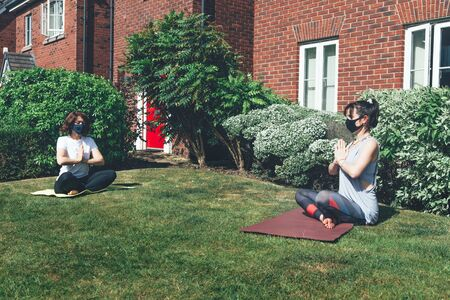 Two woman are doing yoga while wearing face masks and keeping the social distance at the garden, stay home and keep the distance concept, new normal