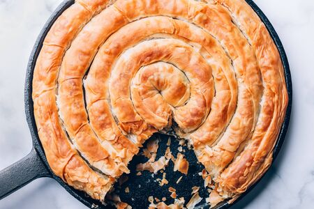Filo Spinach and Feta Twist Pie in the iron pan after oven. Authentic Greek bakery. With spinach, mizithra and feta cheeses.
