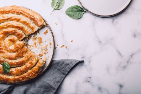 Filo Spinach and Feta Twist Pie in the plate freashly baked at home Фото со стока - 150102337