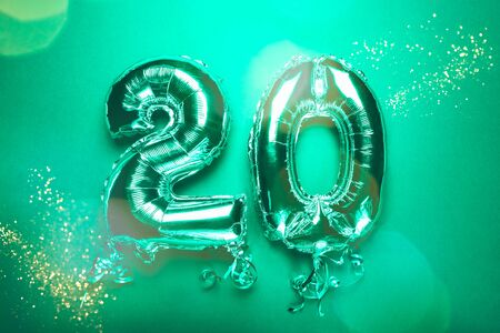 Silver Number Balloon 20 on green background. Holiday Party Decoration or postcard concept with top view on green background