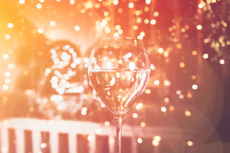 Cheers. Glass of champagne for New Year 2021 celebration. Beautiful christmas lights on the background Archivio Fotografico