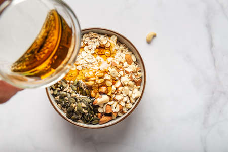 Ingredients for healthy homemade granola with Gluten Free Rolled oats or porridge oats, variety of chopped nuts and seeds, and maple syrup. Preparation for cooking at home, all mixed in bowl.
