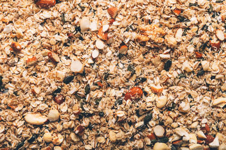 Raw healthy homemade granola with Gluten Free Rolled oats or porridge oats, variety of chopped nuts and seeds, and maple syrup. Preparation for cooking at home before roasting in oven. Фото со стока
