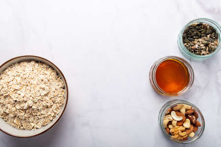 Ingredients for healthy homemade granola with Gluten Free Rolled oats or porridge oats, variety of chopped nuts and seeds, and maple syrup. Preparation for cooking at home. Marble background Фото со стока