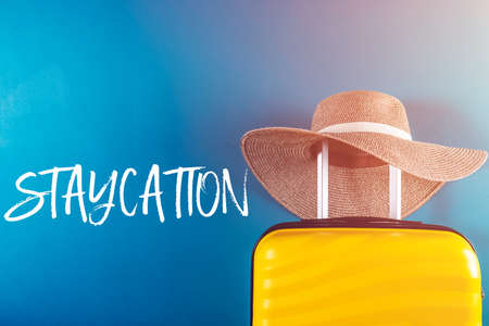 Staycation word. Bright and stylish cabin size suitcase with straw hat against bright blue background. Easy travel at home country during coronavirus outbreak with little baggage concept.