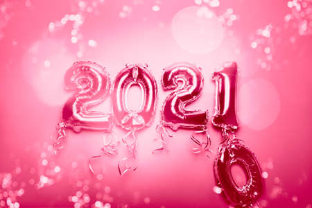 Cnanging of Year 2020 to New Year 2021 made from Silver Number Balloons. Holiday Party Decoration or postcard concept with xmas lights, on pink background