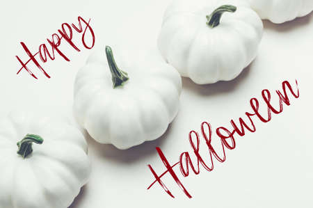 Happy Halloween text. White Pumpkins on light background as minimal autumn concept, flat lay, top view