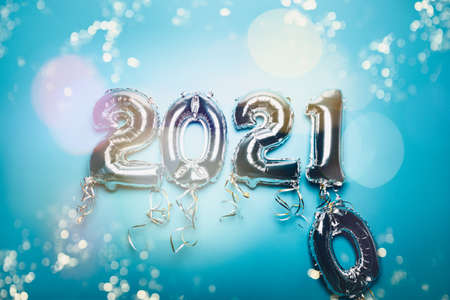 Cnanging of Year 2020 to New Year 2021 made from Silver Number Balloons. Holiday Party Decoration or postcard concept with xmas lights, on blue background