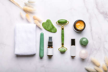 Set of Gua Sha massage tools for beauty facial therapy, Skin Care Anti-Aging Tools such as Green Aventurine and Rose Quartz Mushrooms, Wand, Jade face roller, stone and bottles of cosmetics
