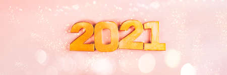 Happy New Year 2021. Golden digits 2021 are on pink background. Holiday Party Decoration or postcard concept with top view and copy space, banner size