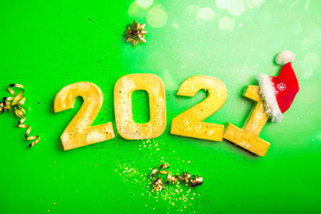 Happy New Year 2021. Golden digits 2021 with christmas hat are on green background with glitter. Holiday Party Decoration or postcard concept with top view and copy space.
