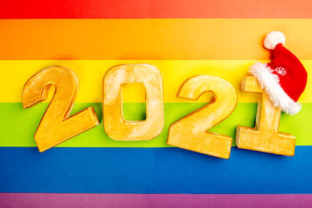 Happy New Year 2021. Golden digits 2021 with christmas hat are on LGBT rainbow flag background. Holiday Party Decoration or postcard concept with top view and copy space. Stock fotó