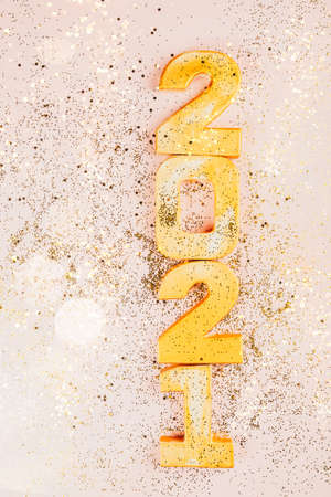 Happy New Year 2021. Golden digits 2021 with glitter and xmas decorations nearby. Holiday Party Decoration or postcard concept with top view and copy space.