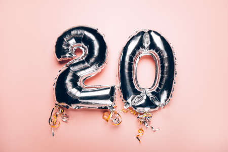 Silver Number Balloons 20 on pink background. Holiday Party Decoration or postcard concept with top view on pink background