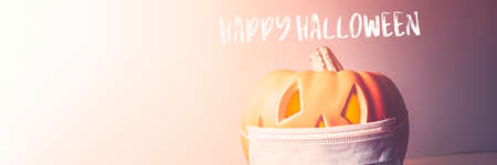Happy Halloween 2020 text. Orange Pumpkin or Halloween Jack o Lantern in medical protective mask, halloween and covid-19 concept. New Normal and New reality concept. banner size Imagens