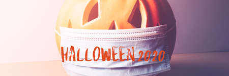 Halloween 2020 text. New Normal and New reality concept. Orange Pumpkin or Halloween Jack o Lantern in medical protective mask, halloween and covid-19 concept, banner size Imagens