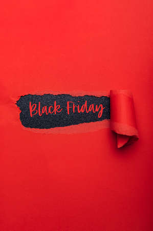 Black Friday text in paper hole. Red torn paper with black paper as background