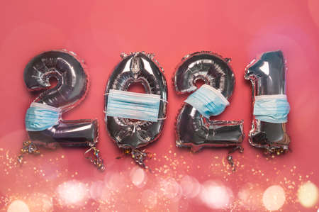 Balloon Bunting for celebration of New Year 2021 made from Silver Number Balloons with protective face masks on pink background. Holiday Party Decoration or postcard concept as New Reality
