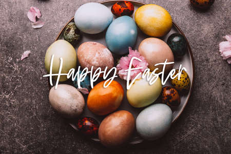 Happy Easter words.. Easter eggs dyed in pastel colors with natural ingredients from red cabbage, onion, spinach, berries, turmeric, coffee. Homemade naturally dyed eggs.