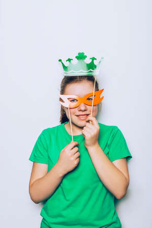 Young girl is preparing for the St Patricks Day party with photo booth props, Ireland traditional holiday, 17 March