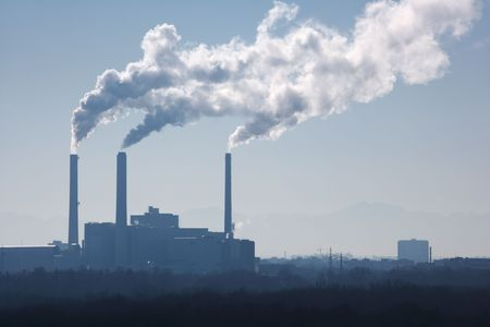 silhouette of power plant with smoke stacks