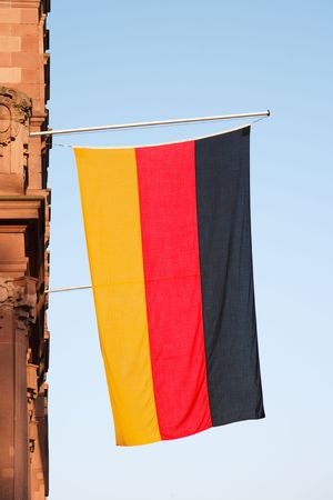 german flag hanging vertical against blue sky
