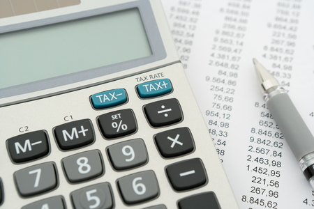 home expenses: close up of calculator and document with pen, focus on blue tax buttons