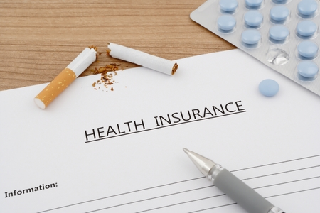 broken contract: health insurance document with pills and broken cigarette on wooden table Stock Photo