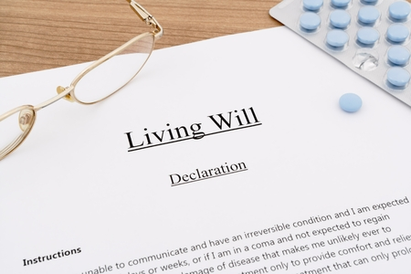 living will with pills and eyeglasses on wooden table