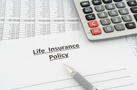 life insurance policy with numbers, calculator and pen