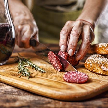 伝統的なイタリアの赤ワイン、サラミ、ローズマリー、パン。キッチン ボードにサラミを切る人の手のクローズ アップ。ディナー 写真素材