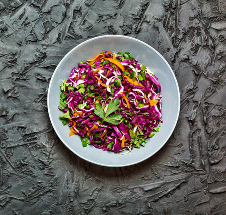 Salad, healthy food. Red cabbage salad. Fresh vegetable salad with purple cabbage, white cabbage, salad, carrot in a dark clay bowl on a black background. View from above, movie effect Stock Photo