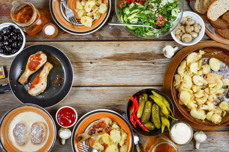 Dinner table with roasted chicken legs with fried potatoes, chimchiuri and chili sauce, grill bean and broccoli as a side dish over old wooden table. Top view. holiday