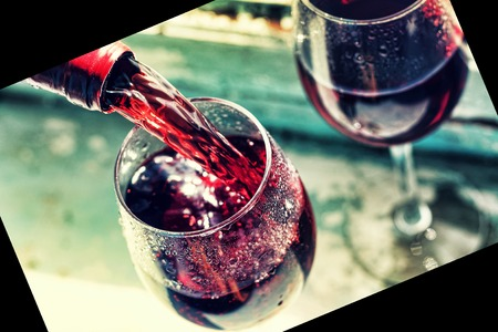 pouring red wine. Wine in a glass, selective focus, motion blur, Red wine in a glass. Sommelier pouring the wine into the glass. Thanksgiving Day, Valentines day, date, love, Celebration. Stock Photo