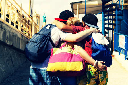 Happy friends hug. Happy friends embrace. Concept: a holiday in the summer. Vacation, travel. A company of young people are resting together in a seaside resort. Happy friends embrace.
