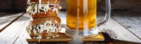 A mug of light beer and a huge burger closeup