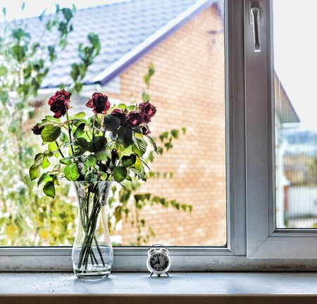 A bouquet of beautiful roses on the windowsill in the house. Concept: Love, St. Valentines Day, Birthday, anniversary of the wedding.
