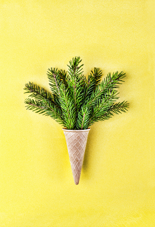 Christmas. New Year. Style minimalism. Christmas tree in ice cream cone on a yellow background.close up