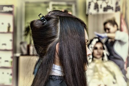 groomed: Beauty saloon. Healthy well-groomed hair. Young beautiful woman dyes her hair in a beauty salon.