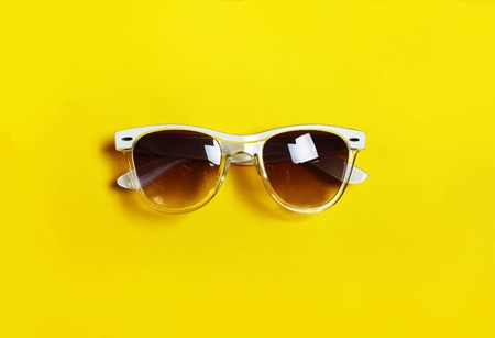 The concept of minimalism. Hipster glasses. White frame. Yellow background. top veiw Stock Photo