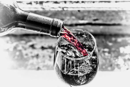 pouring red wine. black and white.Wine in a glass, selective focus, motion blur, Red wine in a glass. Sommelier pouring the wine into the glass. Thanksgiving Day Stock Photo