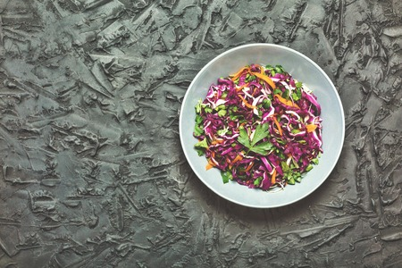 Salad, healthy food. Red cabbage salad. Fresh vegetable salad with purple cabbage, white cabbage, salad, carrot in a dark clay bowl on a black background. View from above