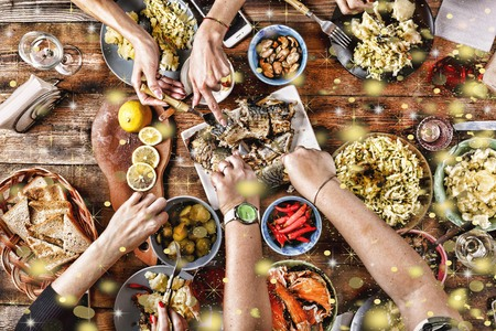 Christmas dinner. Falling golden snowflakes. Cheers Top of view of a nicely served wooden table Christmas dinner with tasty dishes and snacks, friends are toasting with glasses of red and white wine. top veiw